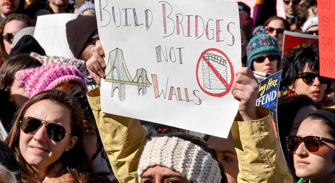 Protester holding a sign which says Build bridges, not walls