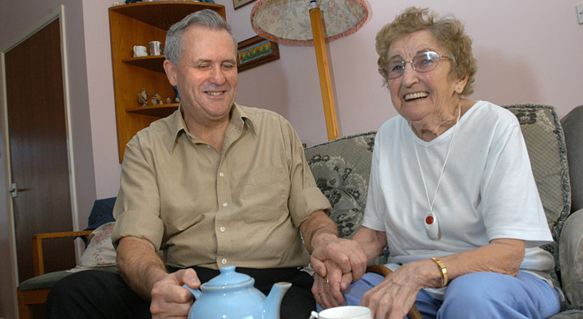 An old woman and her carer sitting on sofa, drinking tea