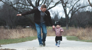 Photo of a father and a child running in the park