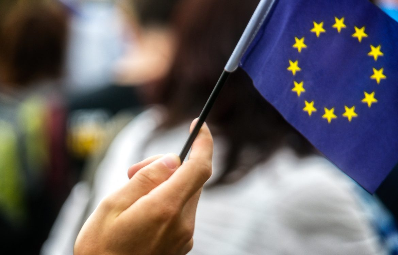 Hand waving EU flag in crowd