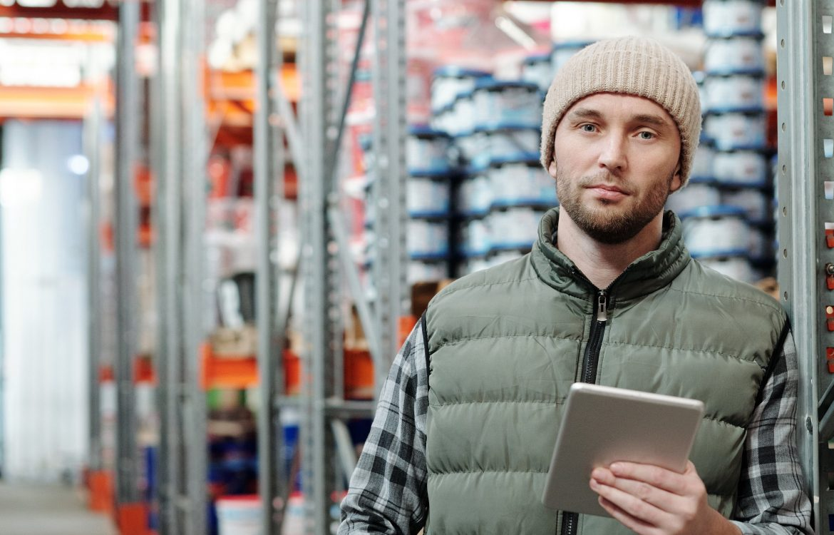 man standing in warehouse with tablet