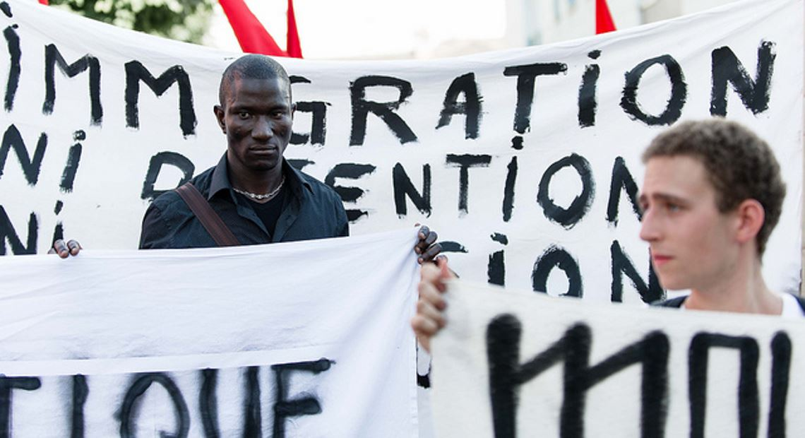 Men standing with banners about migration