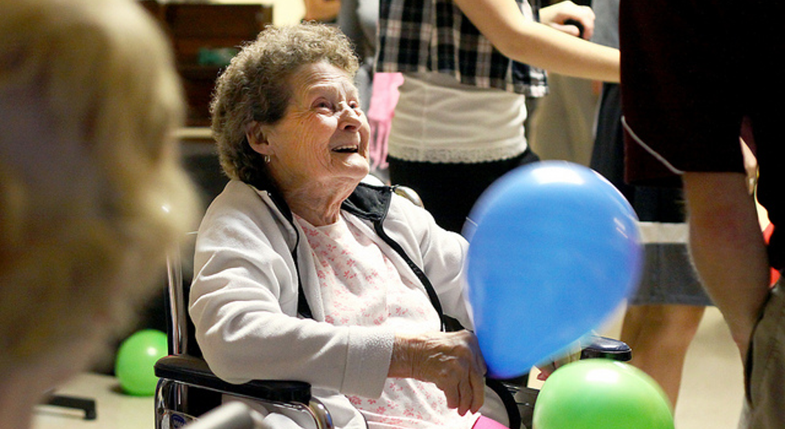 An old lady in the wheelchair holding a balloon and smiling