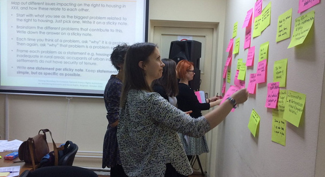 Participants adding post-it notes on the wall