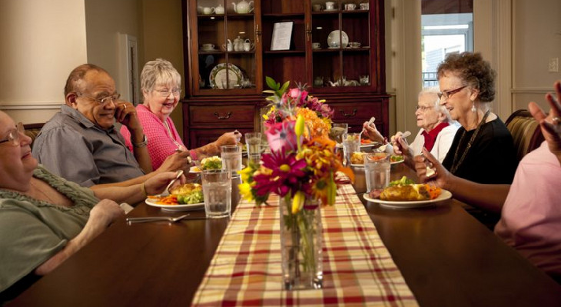 Old people sitting at the dining table and eating