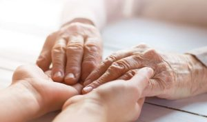 Older person and younger person holding hands